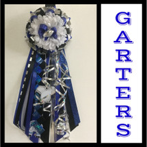 The Royal Blue and Black Homecoming Garter from Enchanted Florist includes a single garter flower, trinkets, metallic chain, the diamond braid and garter band in the school colors of your choice. HMC152