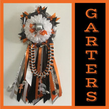 The Orange and Black High Homecoming Garter from Enchanted Florist includes a single garter flower, trinkets, metallic chain, the Love braid with bling and garter band in the school colors of your choice.  HMC153