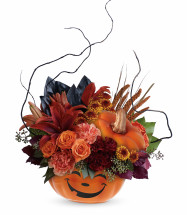 "Halloween Magic Bouquet by Enchanted Florist.   Item T15H100  This magical bouquet features rust-colored asiatic lilies, orange carnations, miniature maroon carnations, brown button spray chrysanthemums, magnolia leaves, burgundy copper beech, seeded eucalyptus, lemon leaf, curly willow and dried brown china millet. Delivered in a Halloween Magic Pumpkin container. Approximately 15"" W x 19 3/4"" H"