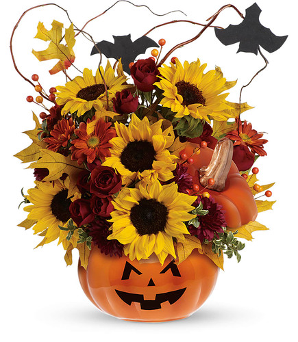 Trick & Treat Halloween Pumpkin Bouquet by Enchanted Florist. A spooky pumpkin filled with red spray roses, bright yellow sunflowers, orange daisy spray mums and curly willow make this bouquet so beautiful, it might even be scary! It's accented by two black bats and nestled inside our popular ceramic pumpkin, complete with a jack-o-lantern face. Send a Happy Halloween smile to someone on your friend's list.  ITEM T12H100