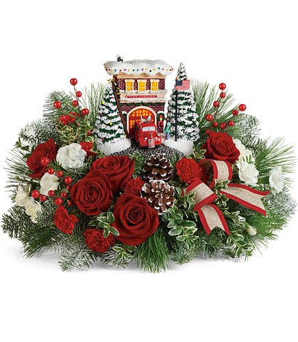 Thomas Kinkade's Festive Fire Station Bouquet 2019. Capture the vintage charm of small-town Christmas with this this festive Thomas Kinkade fire station sculpture. Set atop an arrangement of red roses and fresh winter greens, the hand-painted keepsake lights up for years of fun! T19X200