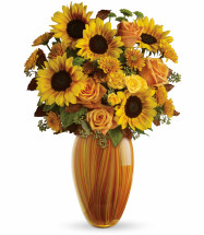 "Sunset Beauty Sunflower Bouquet by Enchanted Florist. This stunning hand-blown art-glass vase is a high-style masterpiece and a wonderful keepsake for years to come. The distinctive bouquet includes orange roses, yellow spray roses, yellow cheerful sunflowers, green button mums, and orange cushion spray chrysanthemums accented with assorted greenery.  Approximately 18"" W x 21"" H SKU RM210"