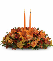 Thankful Thanksgiving Centerpiece by Enchanted Florist. When your loved ones gather around the table, let them bask in the warm glow of two orange taper candles surrounded by a beautiful array of fall flowers and accents. T169-1