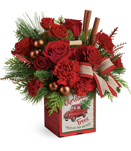 Merry Vintage Christmas Bouquet hand delivered from Enchanted Florist. Wish them a merry vintage Christmas with this happy holiday bouquet of fresh holiday blooms and winter greens delivered in this charming distressed metal cube adorned with a vintage red truck pictured.  SKU T19X600 DELUXE