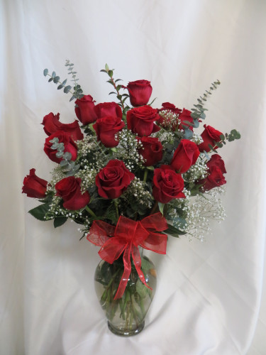 Love and Devotion 2 Dozen Red Roses by Enchanted Florist Pasadena TX. This show stopping bouquets of our classic red Ecuadorian roses comes complete with greens, baby's breath and a bow and is hand arranged by our premier floral designers. RM371