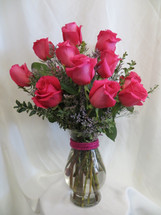 HOT Momma Dozen Hot Pink Roses by Enchanted Florist Pasadena TX - One dozen long stems hot pink roses are arranged in a vase with baby's breath and ribbons as pictured. Don't make you special someone design her own flowers from a box! Our beautiful Ecuadorean roses are hand designed by expert floral artisans.  RM373