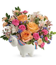 Unicorn Magic Flower Bouquet from Enchanted Florist. Peach roses, pink spray roses, white alstroemeria, peach miniature carnations, blue sinuata statice, and pink waxflower are accented with huckleberry and pitta negra. Delivered in a Charmed Unicorn Keepsake they will treasure for a lifetime. TEV58-4