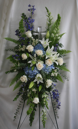 Large Crystal Cross Standing Spray from Enchanted Florist. This special spray includes blue hydrangea, white roses, white oriental lilies, white alstroemeria, bells of Ireland, blue delphinium, white snapdragons, eucalyptus, and and assorted greenery foliages. Delivered on a wire easel with a Large Crystal Cross Keepsake. SKU 561