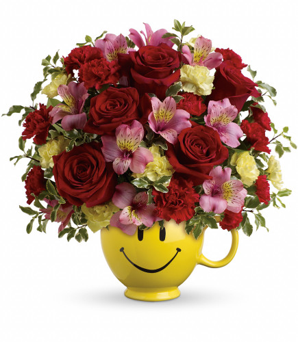 So Happy Smiley Face Mug with Red Roses from Enchanted Florist. This smiley face mug features red roses, pink alstroemeria, miniature red carnations, miniature light yellow carnations and greenery. It comes hand delivered our exclusive Be Happy Mug. SKU RM181