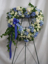 Blue Heart Funeral Tribute Flower Spray by Enchanted Florist Pasadena TX. Accented with trailing ivy, this sweet heart-shaped wreath of sky blue hydrangea, white big roses and pure white mini spray roses is a loving remembrance. SKU RM563