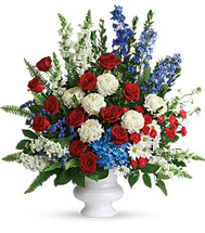 "Patriotic Funeral Flowers Arrangement by Enchanted Florist Pasadena TX. A patriotic mix of all-American red, white and blue flowers such as hydrangea, roses, miniature carnations, snapdragons, mums and more are perfectly arranged in a white urn. Approximately 31"" W x 34"" H SKU RM573"
