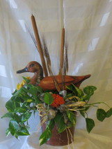 "Duck Decoy Ivy Plant from Enchanted Florist. The classic pothos ivy green plant gift includes a styrofoam duck decoy, cattails, wheat and a matching bow. Plant gift is approximately 18""H x 12""W.   SKU RM445"