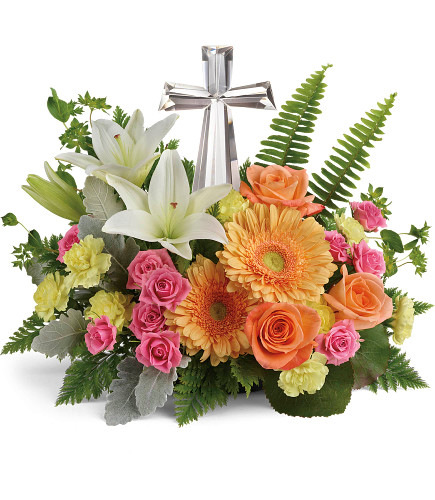 """Bright Petal Large Crystal Cross Sympathy Flowers from Enchanted Florist. Our funeral flower arrangement includes pink spray roses, white oriental lilies, light orange gerbera daisies, and yellow miniature pixie carnations and is accented with various greenery including galax leaves, sword fern, and leatherleaf fern. Delivered with the large crystal cross keepsake. Cross is approximately 11""""H x 6""""W x 2""""D. Sympathy flower arrangement is approximately 16"""" W x 13"""" H SKU RM578"""