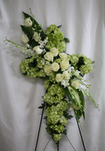 "Green Hydrangea & White Rose Funeral Cross Flowers from Enchanted Florist.  Stunning funeral flowers such as white roses, white orchids, and green hydrangeas along with carefully selected foliage create a beautiful cross that is full of love and devotion, arriving on a wire funeral easel. Approximately 223"" W x 34"" H  SKU RM502"