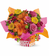 """Birthday Present Flower Bouquet from Enchanted Florist. Gorgeous pink roses, hot pink spray roses, orange asiatic lilies, sunny yellow miniature gerberas, green button spray chrysanthemums and more fill a gift box. Ribbons. Roses. Radiant! Approximately 16 3/4"""" W x 13 1/2"""" H SKU T20-1"""