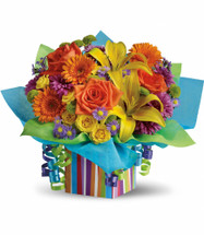 """Birthday Present Flower Bouquet from Enchanted Florist. Stunning orange roses and miniature gerberas, yellow spray roses and asiatic lilies, purple monte cassino asters and cushion spray chrysanthemums plus green button spray chrysanthemums and more are all wrapped up in a ribboned, striped gift box. Colorful and classy! Approximately 17"""" W x 14 1/4"""" H SKU T20-1"""