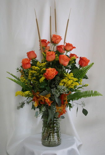 "Fall Orange Dozen Roses with Yellow Solidago from Enchanted Florist. Your fall fanatic will love this Autumn themed dozen roses, a traditional flower gift with a twist. This colorful standard roses includes the vibrant orange roses with contrasting yellow solidago filler, fall leaves and mini cattails to accent. Approximately 18""W x 27""H SKU RM211"