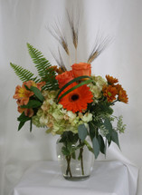 """Autumn Dew Drops Bouquet in Orange from Enchanted Florist. Your beautiful fall bouquet will arrive in a clear vase and includes hydrangeas, orange roses, orange gerbera daisies, alstromeria and butterscotch daisies and is accented with sword fern and wheat grass. Approximately 13""""W x 17""""H SKU RM212"""