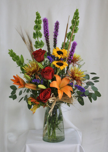 """Fantastically Fall Red Rose Bouquet from Enchanted Florist. Your fall arrangement includes orange Asiatic lilies, sunflowers, red roses, purple liatris, bronze spiders, bells of Ireland and assorted greenery for a fall floral bouquet to enjoy. Approximately 18""""W x 30""""H SKU RM214"""