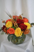 "Autumn Harvest Fall Bouquet with Red Yellow and Orange Roses from Enchanted Florist. Your fun and flowery bouquet will include a mixture of red roses, orange roses, and yellow roses and are accented with festive orange wax flower, seeded eucalyptus and wheat for a fun fall look. Approximately 12""W x 13""H SKU RM215"