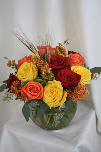 """Autumn Harvest Fall Bouquet with Red Yellow and Orange Roses from Enchanted Florist. Your fun and flowery bouquet will include a mixture of red roses, orange roses, and yellow roses and are accented with festive orange wax flower, seeded eucalyptus and wheat for a fun fall look. Approximately 12""""W x 13""""H SKU RM215"""