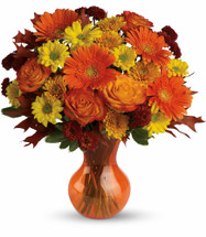 "Forever Fall Orange Rose Bouquet from Enchanted Florist. Our spectacular bouquet includes orange roses, orange gerberas, yellow daisy mums, orange cushions and rust buttons accented with fresh greenery. Delivered in a sparkling orange Serendipity vase. Approximately 16"" W x 16"" H SKU RM221"