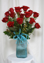 """Turquoise Vase with Red Rose Bouquet from Enchanted Florist. This beautiful bouquet of roses includes 15 premium red roses arranged along side red huck and adorned with a turquoise bow and arrives in our beautiful exclusive turquoise art vase. Approximately 24""""H x 16""""W SKU RM356"""