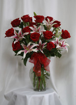"Grand Love Stargazer and 15 Red Roses Bouquet from Enchanted Florist. Our beautiful and popular bouquet includes 15 beautiful Ecuadorian red roses designed in it alongside fragrant stargazer lilies and accented with a red sheer bow. Approximately 25""H x 16""W SKU RM362"