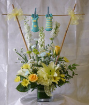 Baby Boy Clothesline Flower Bouquet with Socks by Enchanted Florist Pasadena TX. The adorable bouquet includes yellow roses, yellow oriental lilies, white larkspur, & yellow daisies in a yellow & white theme. SKU RM319
