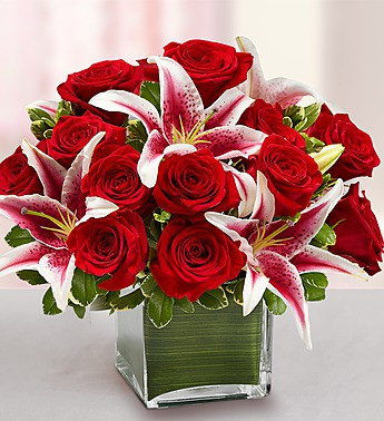 Red Roses and fragrant Starfighter Lilies wrapped in a Green Leaf and delivered in a clear glass cube.