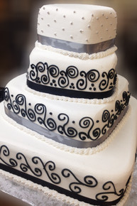 "4 tier spiraling squared cake  serves approximately 150 People  The sizes approximately 17""x17"", 12""x12"", 8""x8"" & 5""x5""  Satin Ribbon, Swirls piped with cream"