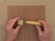 Apply pressure to the veneered surface using a one inch wallpaper seam roller