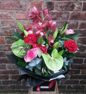 An exquiste handtied aquapac bouquet of flower delight. Featuring a large cymbidium orchid, anthuriums, red roses, pink roses and oriental lillies. Beautifully packaged and presented, including an East of India heart tag.