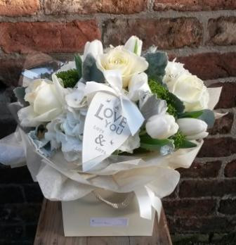 An exquisite handtied aquapac bouquet of pure tones. Featuring avalanche roses, hydrangea, tulips, trachelium and scenicio. Beautifully packaged and presented, including a lovely East of India heart tag.