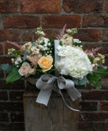 A basket made up of hydrangeas, roses, stocks and bouvardia in the prettiest peach and cream shades. Image of the £40.00 Grand option.