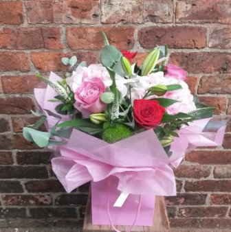 A gorgeous pink and red handtied aquapac bouquet with lilies and roses as the feature.