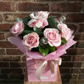 A handtied aquapac bouquet featuring 6 of the finest pink Avalanche roses, arranged with salal leaves and folded aspidistra. Beautifully presented and packaged, including a lovely little East of India heart tag.