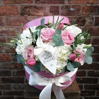 A heavenly display of pretty pinks and creams. Featuring pink charm roses, hydrangea, lisianthus, veronica, tulips and eucalyptus. All arranged together in a luxurious ribboned hatbox, finished off with a lovely East of India heart tag.