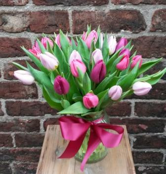 Featuring tulips in a mix of hot pink, lilac and purple. Beautifully arranged in decorative jam jar and finshed off with a satin bow.
