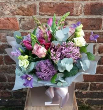 A delightfully scented handtied aquapac bouquet full of garden favourites. Featuring stock, lilac, clematis, lisianthus, rose, veronica, tulip and allium. Beautifully arranged, packaged and presented.