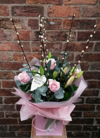 A classic combination. Pink roses and pink lillies in a handtied aquapac bouquet. Featuring fragrant eucalyptus, pussywillow and a lovely East of India heart tag.