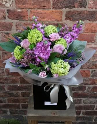 A wonderful vibrant handtied aquapac bouquet featuring a selection of seasonal purple, lilac and lime flowers.