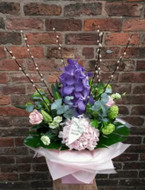 A lavish display of flower. Featuring a truly stunning purple vanda orchid, hydrangea, rose, lily, pussywillow, viburnum, lisianthus, fragrant eucalyptus, aspidistra and monstera. Beautifully arranged and presented with a lovely East of India heart tag.  Image shown is the luxurious option.