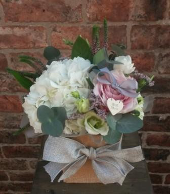 A sweet little gift bag full of flower. Featuring pink roses, hydrangea, lissianthus, veronica, limonium and fragrant eucalyptus. Beautifully arranged in foam and presented in a hessian bag. Including a lovely little East of India heart tag.