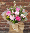 A lovely rustic handtied bouquet of pretty pinks. Featuring roses, Dahlias, Snowberry, Veronica and fragrant Eucalyptus. Beautifully arranged, packaged and presented. Image shown is representative of the standard option. Flowers may change due to season availability.