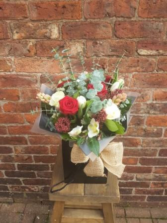 A rustic handtied aquapac bouquet. Beautifully packaged and presented.