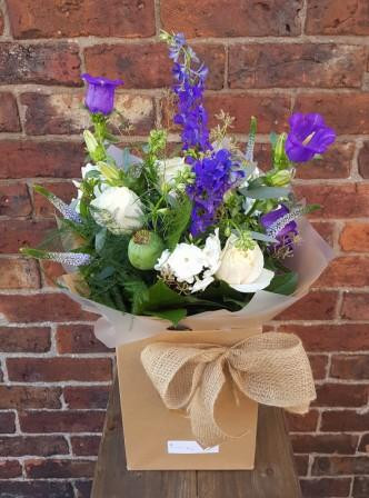 A beautiful handtied aquapac bouquet made up of a seasonal mix of blues and whites.