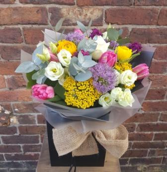 A handtied aquapac bouquet made up of a selection of seasonal flowers. Image shown represents the Luxurious option.