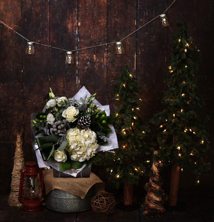 Our 'Winter Dream' bouquet was designed around the idea of that first festive, snowy Christmas morning. It sparkles with Silver Accents that nestle between the White Roses, Hydrangea, Lisianthus and Pinecones. Complementary foliages and berries are slightly dusted with a silver 'frost'.