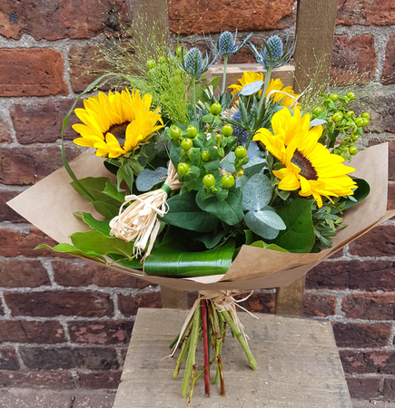 Summer in a bouquet! This Sunflower bouquet has a 'just gathered from the meadow' vibe, and includes vibrant sunflowers, blue eryngium thistle, shiny green hypericum berries and within the foliage included panicum fountain. There is the addition of a little raffia to add to the rustic look. A 'must' for sunflower fans!